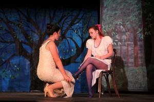 Cinderella's Stepmother (Samantha Ende, left) treis to force Cinderella's slipper onto the foot of her daughter, Florinda (SUmmer Scott).