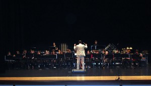 The Middle School Performance Ensemble Band plays on stage under the direction of Mr. Huber.
