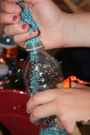 Seventh-grade cheerleader Sydney Steinger makes her shaker by funneling blue rice into one of the Gatorade bottles.
