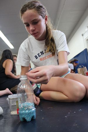 Seventh grader Catherine Schenk adds some glitter to her shaker during the team's practice in the wrestling room.