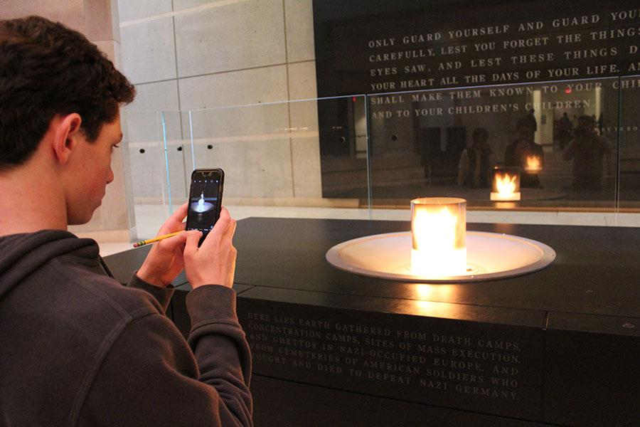 Eighth grader Chase Shapiro takes a photo of the candle  that rests upon a crypt of earth taken from Nazi concentration camps in the Holocaust Memorial and Museum.