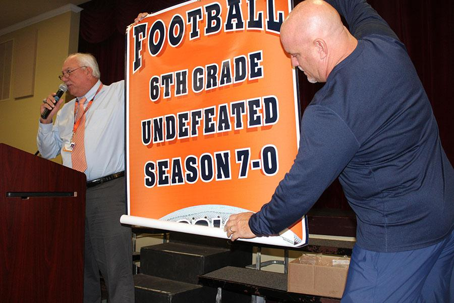 Mr. Harbeck (left) and Mr. Keller unfurl the banner awarded to the sixth-grade football team for their undefeated season.