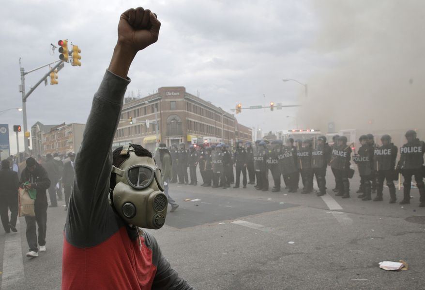 A+demonstrator+raises+his+fist+amidst+the+fires+in+Baltimore%27s+streets+while+police+stand+guard.