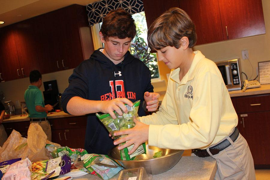 Tommy McCloskey (left) and Christian Baldari  help prepare a salad last year at Quantum House as part of Mr. Bayless and Mrs. Rudner's seventh grade advisories. The students prepared a meal to feed families whose children were being treated at  local hospitals.