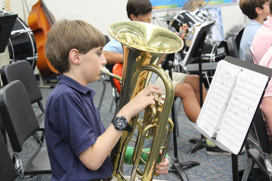 Despite his broken arm (see the green cast?), Mitch is poised to play his best at the All-State Band Concert in January. Here he practices the euphonium during his band class at TBS.