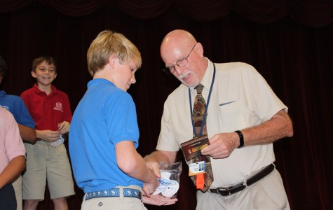 Mr. Mullnix presents an sixth grader Jack Savery with the Most Improved Player Award for football.