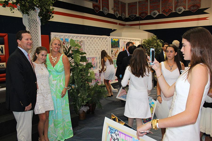 Eighth grader  Emma Johnson (right) photographs fellow classmates Caroline Charles and Charles' parents at the end of the evening.