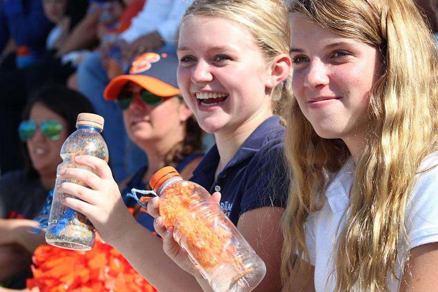 Eighth graders Olivia Cornett (left) and Kate Waxman cheer on the seventh and eighth-grade team using the shakers on September 14.