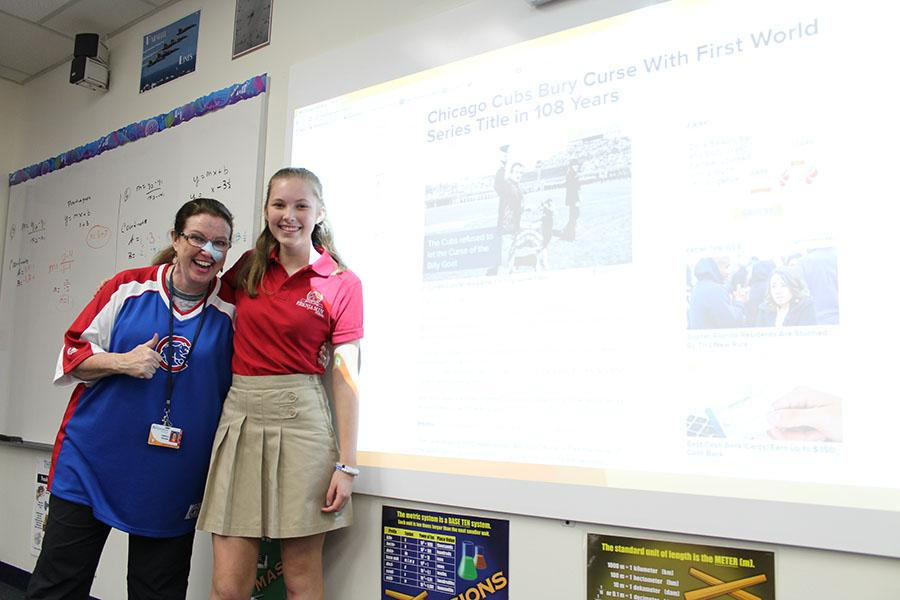 Mrs. Hansen and eighth grader Kate Lower, both Chicago natives, pose next to the interactive white board which touts the fact that the Cubs championship drought has ended.