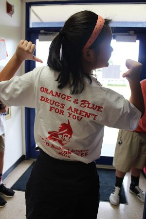 Eighth grader Carol Chen shows off her Red Ribbon Week t-shirt on Friday, October 28.