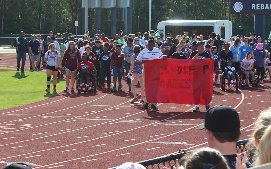 The students who participated in the Friendship Games carry a banner around Reback to kick off the day.