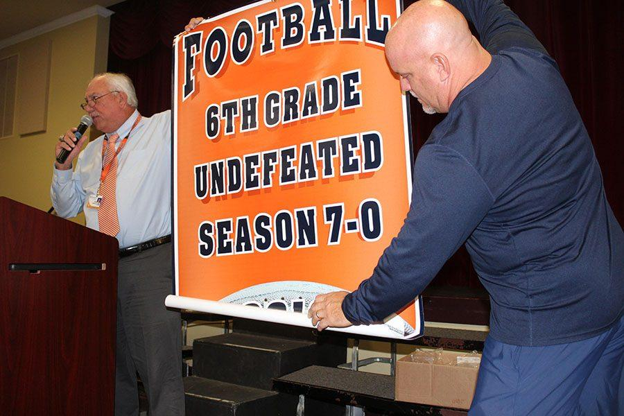 Mr.+Harbeck+%28left%29+and+Mr.+Keller+unfurl+the+banner+awarded+to+the+sixth-grade+football+team+for+their+undefeated+season.