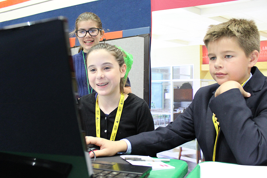 Left to right: Sixth graders Maddie Domnick, Jessica Holland, and Thomas Cornett enjoy working at the bank during their time in BizTown on Friday, February 24.