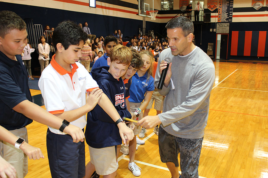 Mr. Cavallo checks to see if all the sixth-grade boys lined up  have watches on. In this competition, the grade level with the most individuals wearing watches were declared the winners.