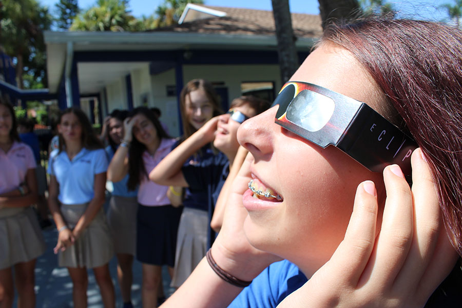Eighth+graders+Ella+Pierman+%28foreground%29+and+Matthew+Postman+%28background%29+test+out+some+of+Ms.+Featherston%27s+solar+glasses+on+Monday+morning+prior+to+the+eclipse.