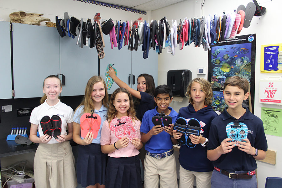 Left to right: Seventh graders Hannah Reece, Holland Poncy, Bella Garaj, Kate Grande, Darren Dharia, Colby German, and Antonio Gambino pose in Mrs. Osters room  with some of the flip flops that students donated.