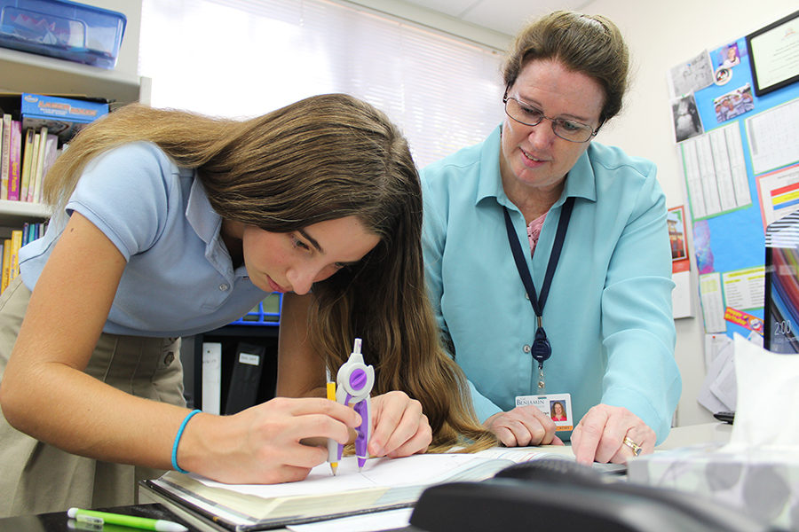 Math Department Chair Mrs. Cathy Hansen helps out one of her advisees, Jane Boyland, during math class.
