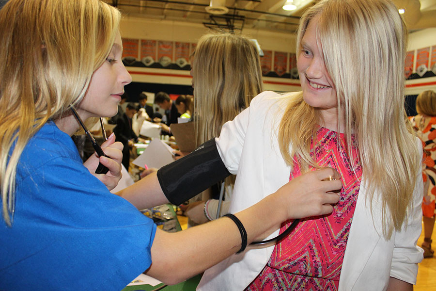 Sixth grader Emma Nordland (left), working as a health and wellness employee, listens to the heartbeat of fellow classmate Winni Cox during their time in BizTown on Friday, December 1.