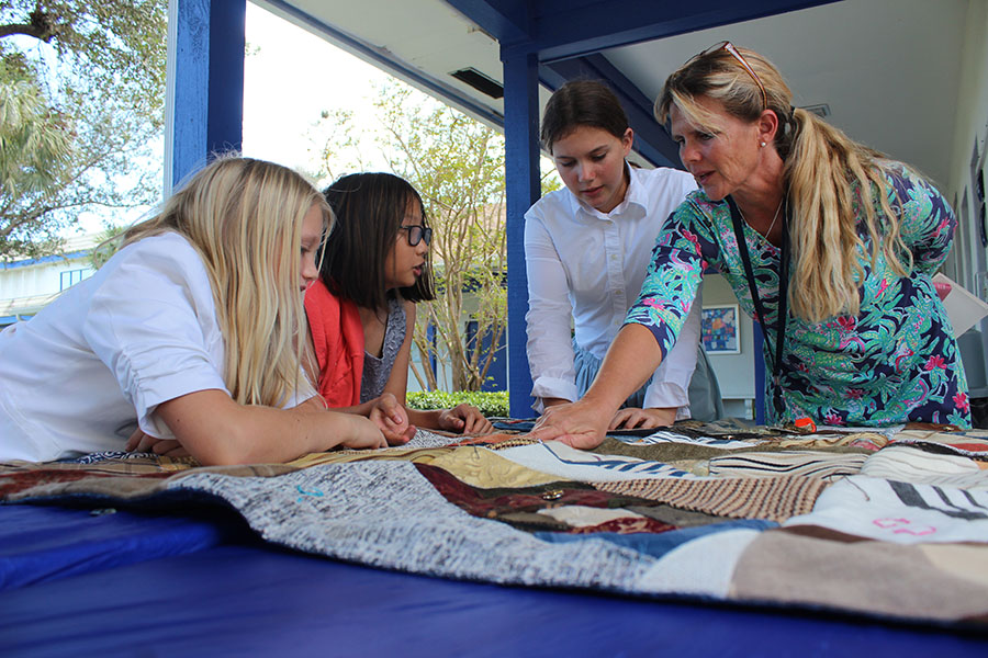 During Heritage Day, sixth graders Winni Cox, Claire Dinh, and Ellie Bickel join lower school science teacher Mrs. Susan Bickel in admiring the craftsmanship of one of the quilts the students sewed.