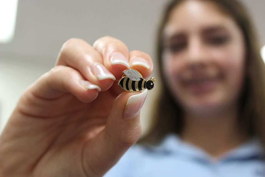 Eighth grader Caroline Yancey holds up her bee pin after winning the contest in Mrs. Devine's E period.