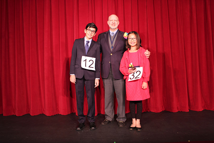 Sixth-grade spelling bee winner Claire Dinh (right) poses with seventh grader and runner-up Kiran Spencer and Head of Middle School Mr. Charles Hagy after the competition in the Barker Performing Arts Center.