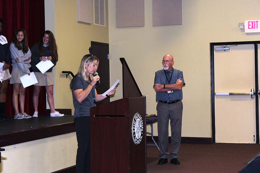 With the team standing on stage behind her, Ms. Filia talks about the girls' basketball season as Mr. Mullnix looks on.