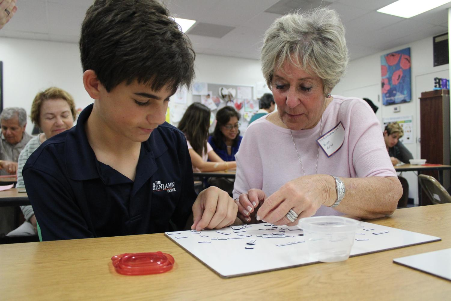 Eighth grader Jake Zur and his grandmother, Wendi Adler, create a poem with magnetic words in Mrs. Devine's room on Grandest Friends' Day.