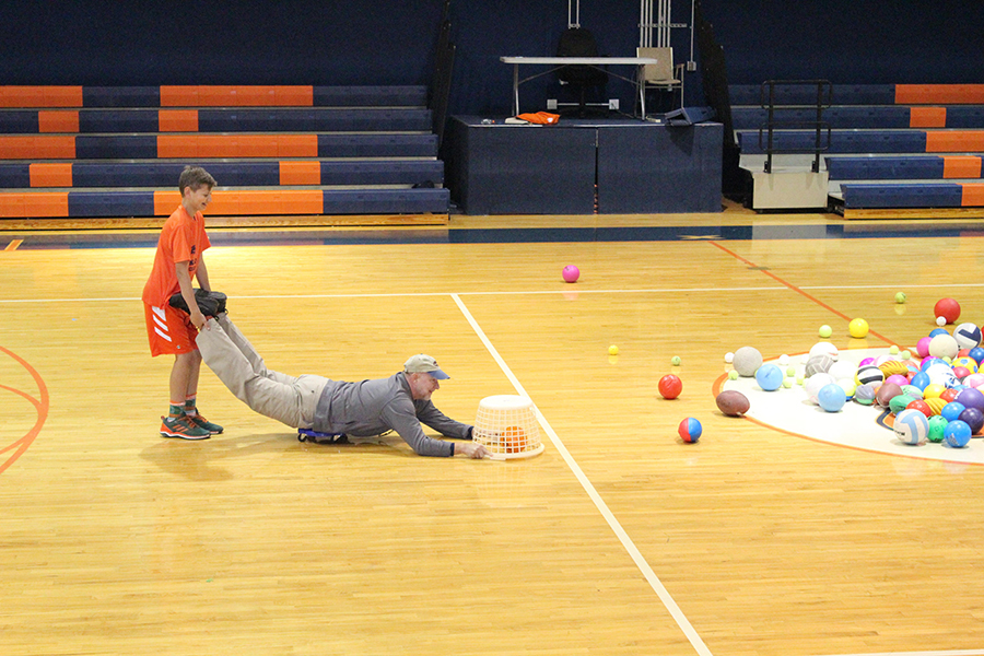 Eighth grader Matthew Postman and Head of Middle School Mr. Charles Hagy demonstrate how to play Hungry Hungry Hippos for the rest of the students.