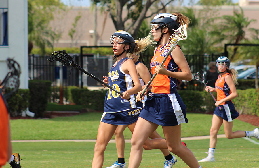 Although concussions are more likely to occur in boys' lacrosse, some female players would welcome a more physical game. Here, eighth grader Eden Josza heads downfield against Palm Beach Day Academy during the league championship on Kennerly Field.