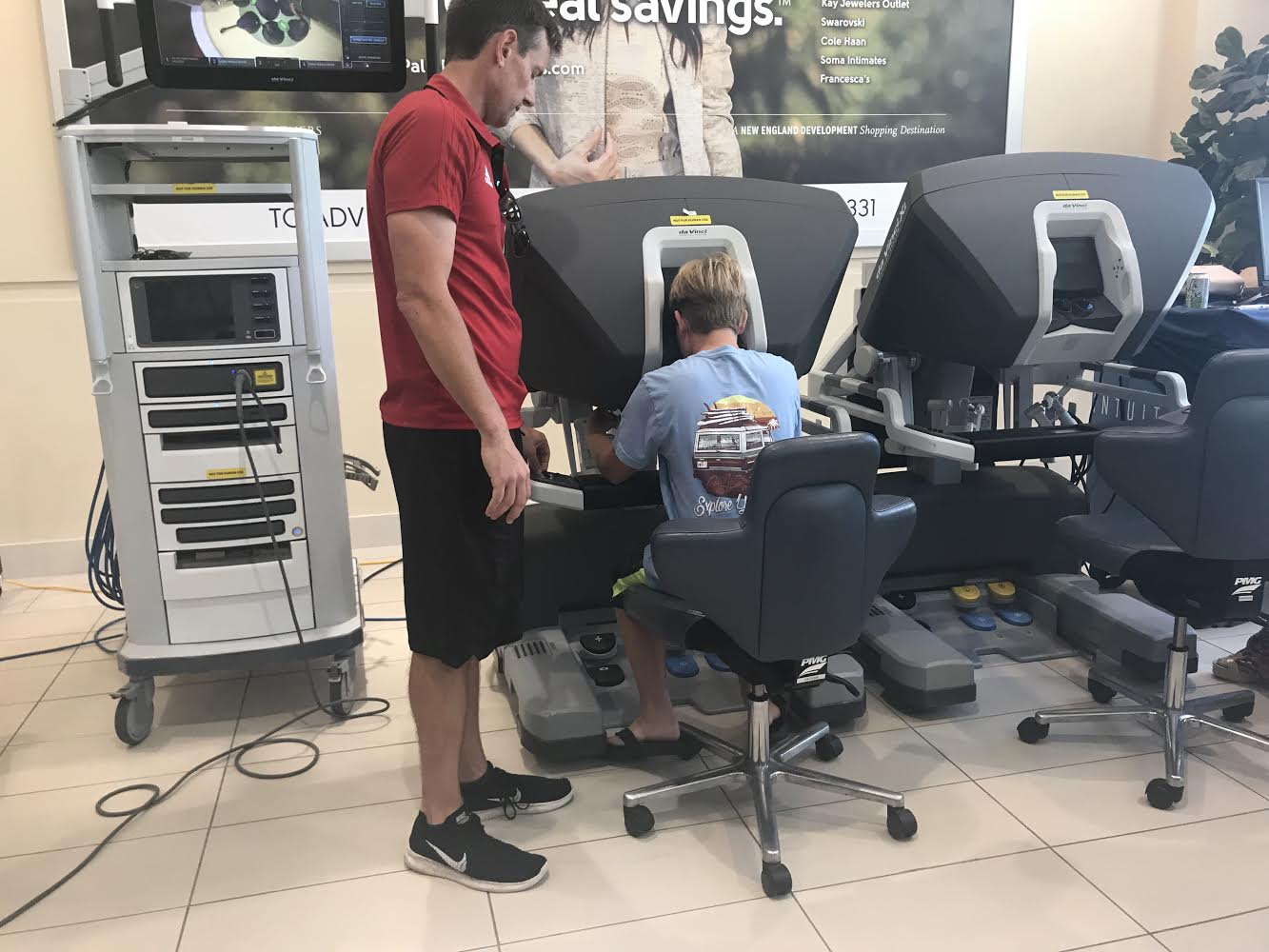With the help of a Good Samaritan Medical Center staff member, sixth grader Colby Mack (seated) tries his hand at controlling the da Vinci Xi.