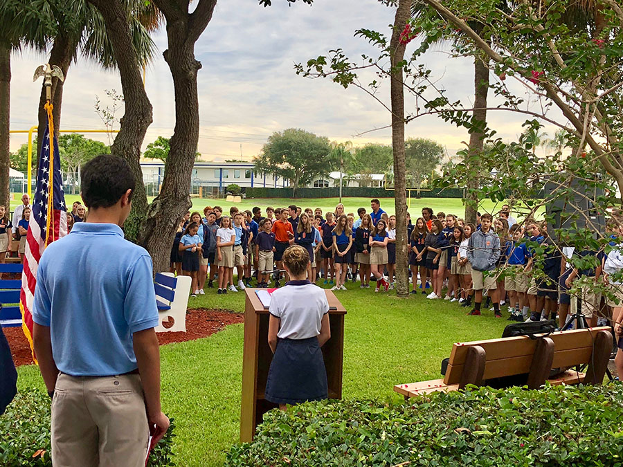 Seventh grader Emerson Ferry reads a portion of President Donald Trump's Patriot Day proclamation to the Middle School in the quad on September 11, 2018.