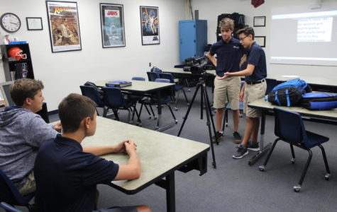 As a part of the eighth-grade class, Intro. to TV Broadcasting, Jasper Wright (mid-ground, right) helps Adam Braman with the camera as they get ready to film Anthony Pace and Antonio Gambino for a segment of TBS News.
