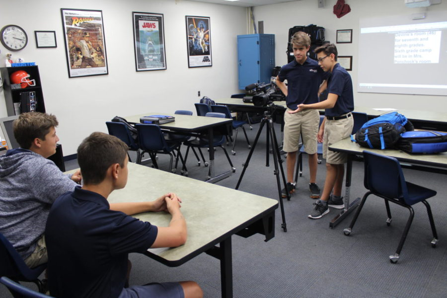 As+a+part+of+the+eighth-grade+class%2C+Intro.+to+TV+Broadcasting%2C+Jasper+Wright+%28mid-ground%2C+right%29+helps+Adam+Braman+with+the+camera+as+they+get+ready+to+film+Anthony+Pace+and+Antonio+Gambino+for+a+segment+of+TBS+News.