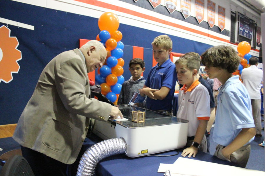 Head of School for Academics Mr. Kendall Didsbury shows off a Glowforge - a 3D laser printer - to sixth graders Cooper Sukhu, Calvin Poncy, RJ Sahm, and Scott Noble.
