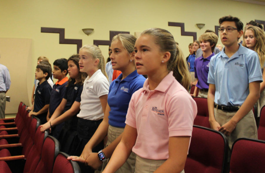 Middle School students stand and sing the alma Mater during assembly in the Barker Performing Arts Center on Monday, October 1, 2018.