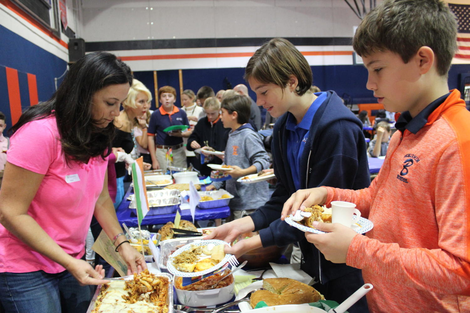 Sixth graders Sofie Odehnalova and Kian Interlandi are served a variety of different foods by parents during the Heritage Day feast.