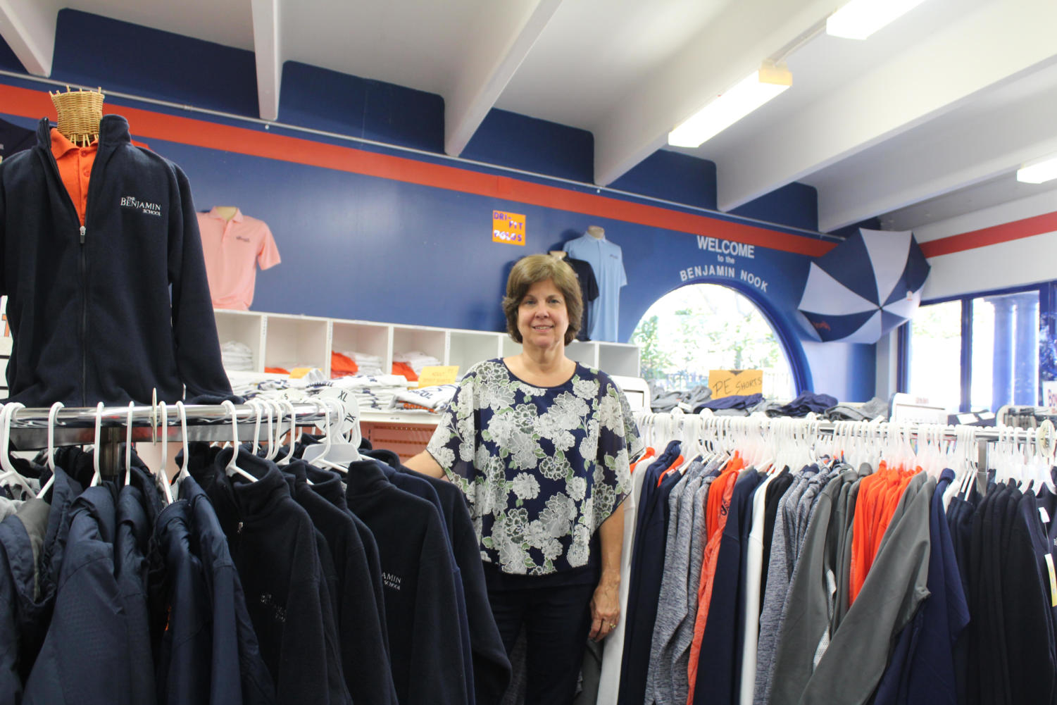 Ms. Rolanda Crawford stands inside the Nook surrounded by the apparel she keeps in stock for TBS families.