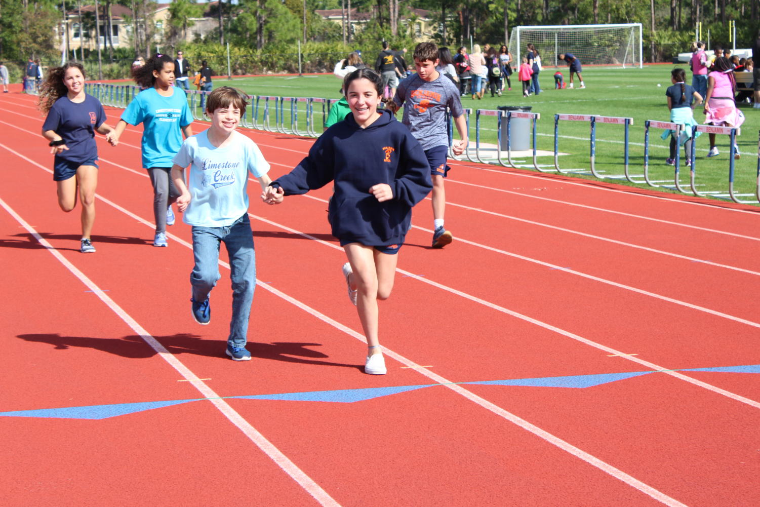 Eighth grader Kate Grande helps a special needs student from Limestone Creek Elementary run the 100-yard dash.