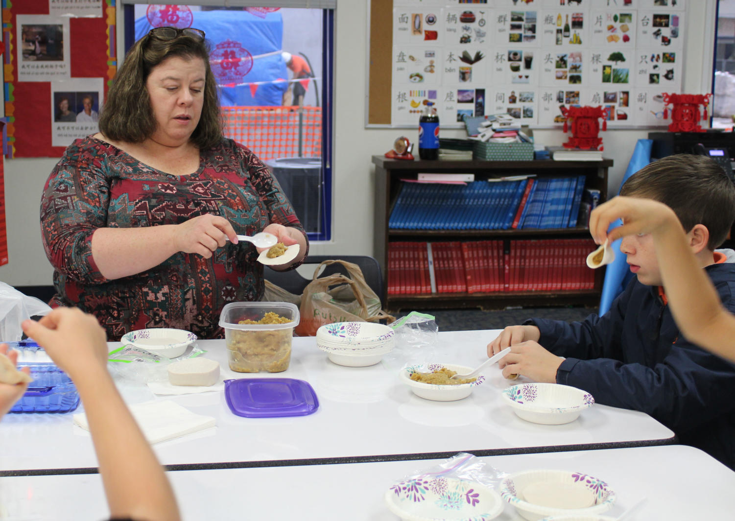 Ms. Latimer helps her students make traditional Chinese dumplings during class on Wednesday, February 13.
