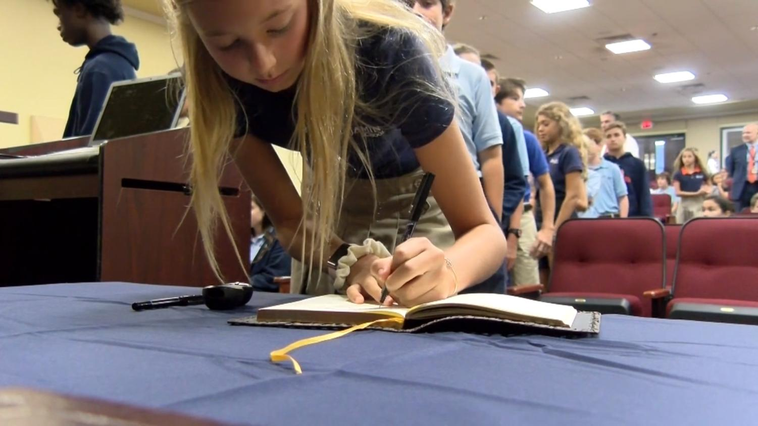 Seventh grader Mimi Chandler signs the honor code book during the Honor Code assembly which TBS News covered in its broadcast.
