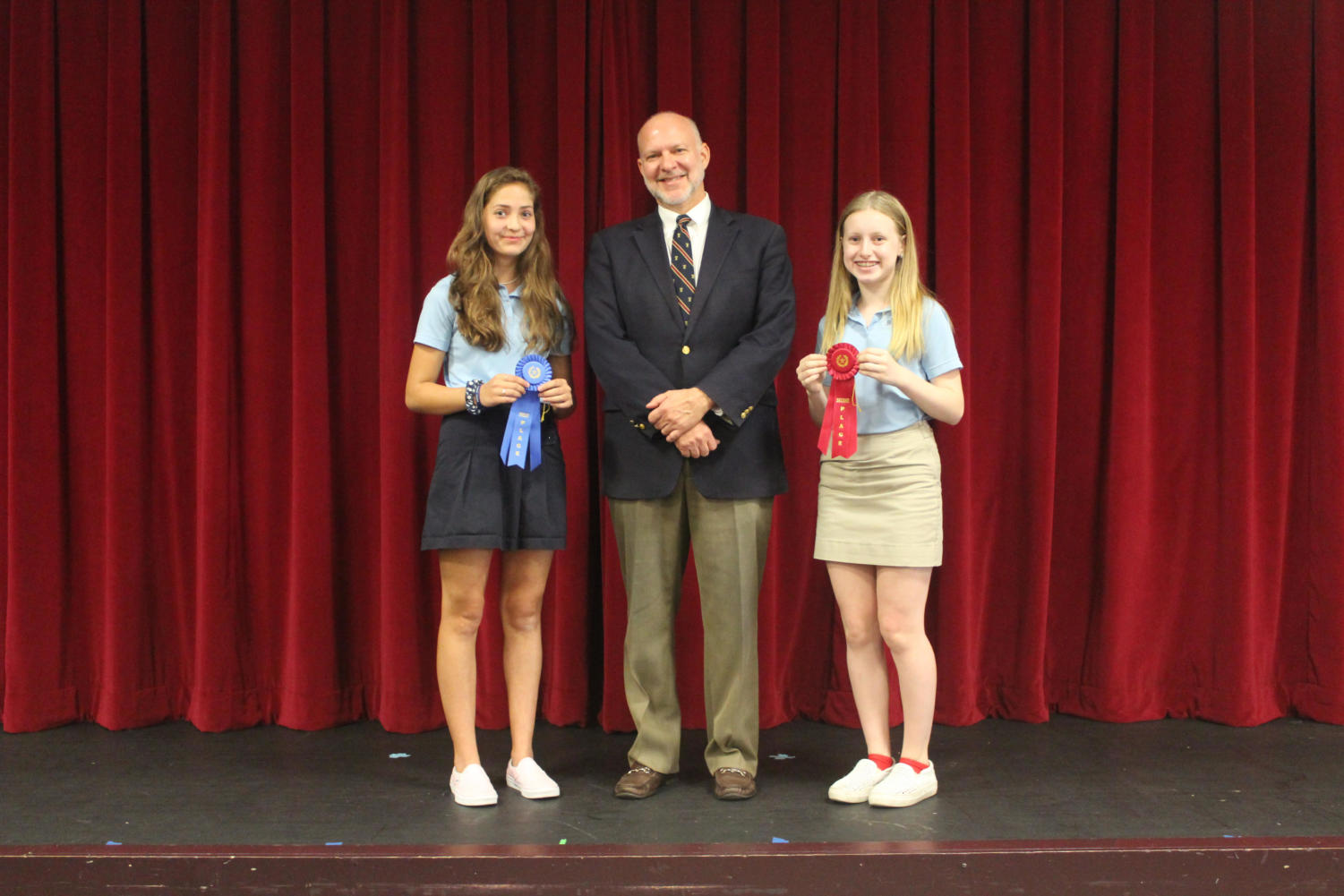 Head of Middle School Mr. Charles Hagy poses with spelling bee champion Emilie Dubiel (left) and runner-up Joie Rodin.