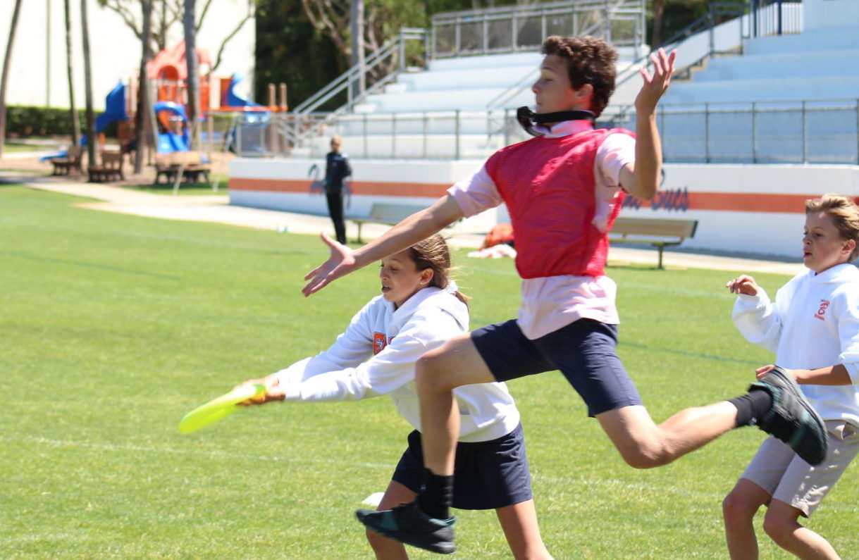 During one of the seventh-grade games, Maggie Smith catches the disc despite the defensive efforts of Brendan Matz as JP Walsh looks on.