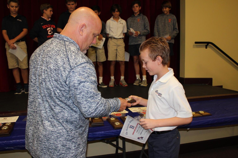 Sixth-grader Matthew Schepp receives his coaches' award from Mr. Keller for the boys' soccer