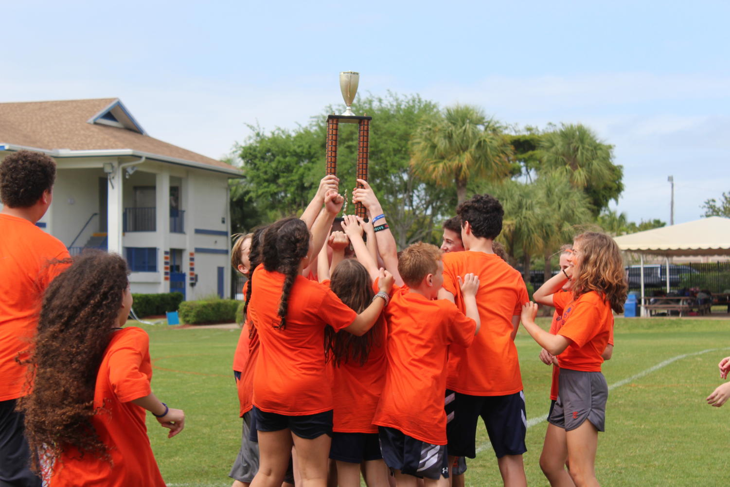 The orange team celebrate its title on Kennerly Field with the trophy after Coach Harbeck announced them winners for the second year in a row.
