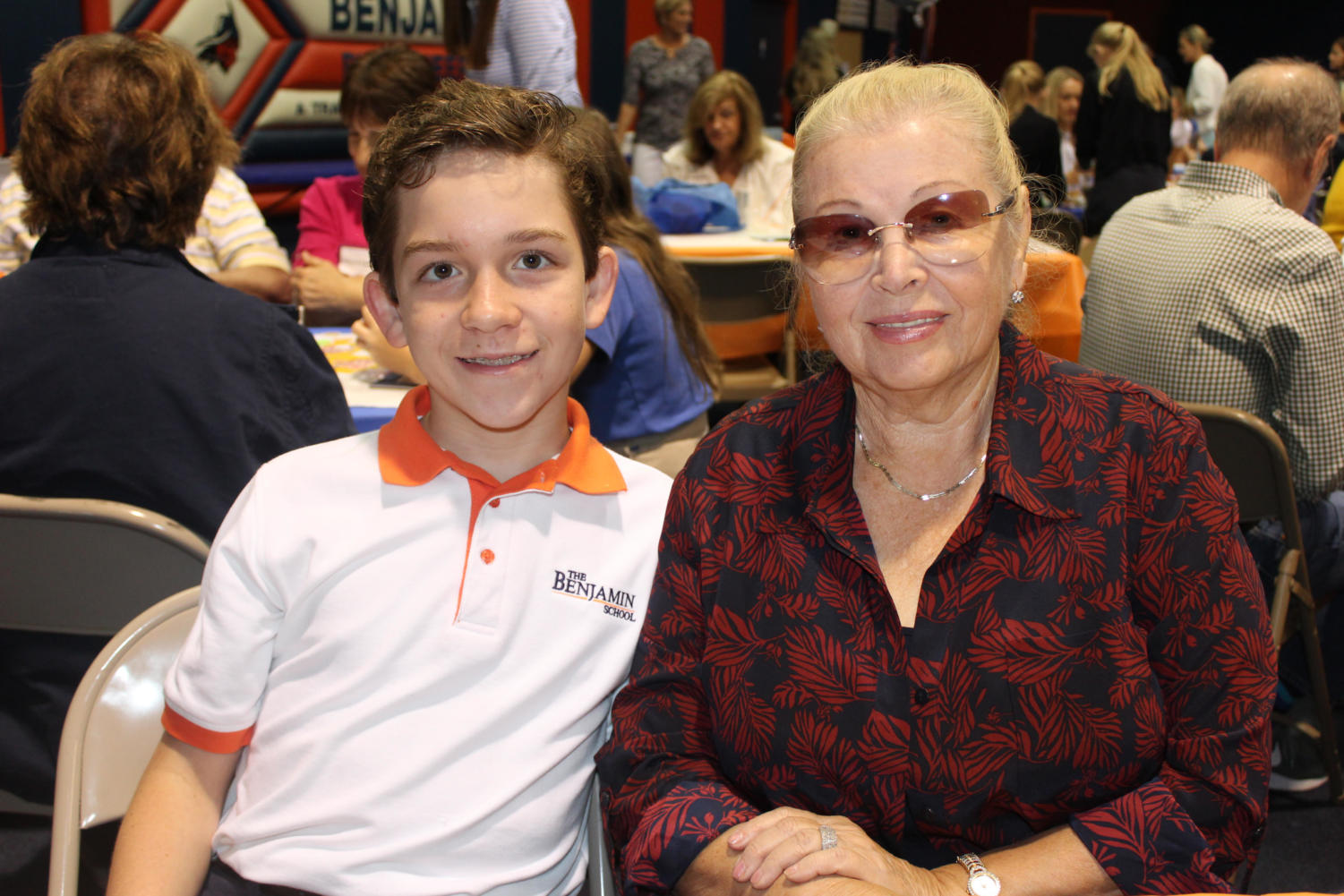 Sixth grader Dany Lovas poses with his grandmother, Ms. Mila Zharmenova, in the gym.