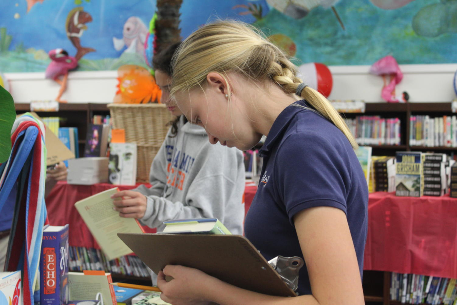 Seventh grader Addie Vining looks for her summer reading books in the library/media center.