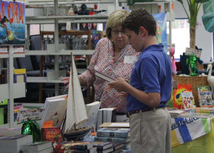 Seventh-grade+student+Arthur+Wolff+checks+out+a+book+at+The+Benjamin+School+Book+Fair.