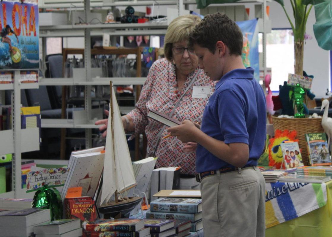 Seventh-grade student Arthur Wolff checks out a book at The Benjamin School Book Fair.