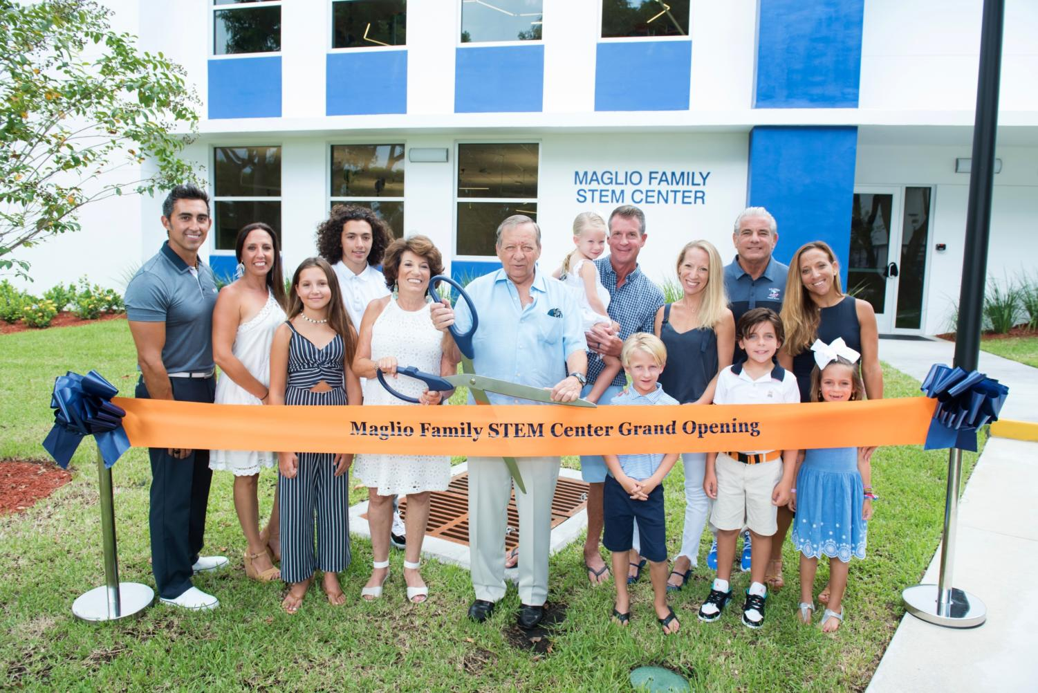 The Maglio and Grande families prepare to cut the ribbon which officially opened the STEM center on August 11, 2019.