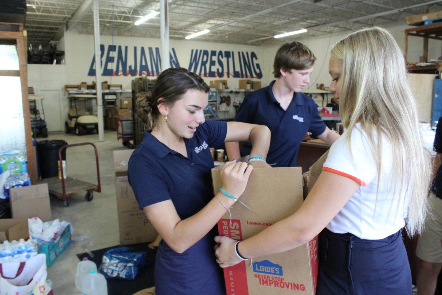 Eighth graders Talia Miller and Taylor Graue pack up boxes of supplies in the maintenance building on September 6, 2019.